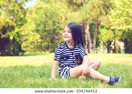 Happy little girl on the green grass in the park