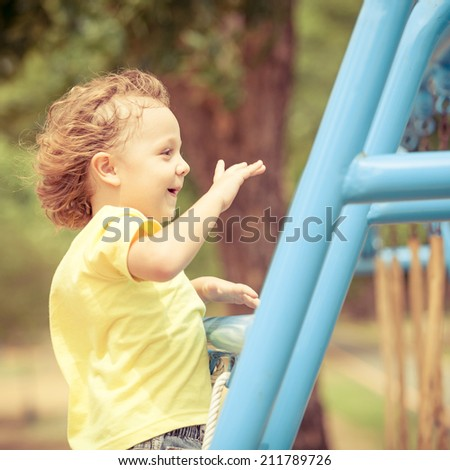Happy little girl on the playground at the day time - stock photo