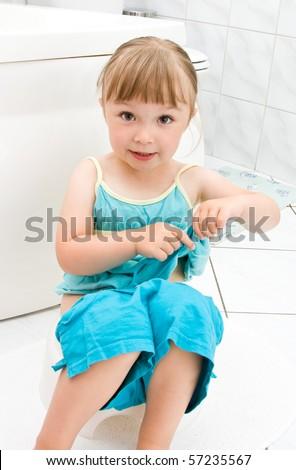 happy little girl on toilet - stock photo