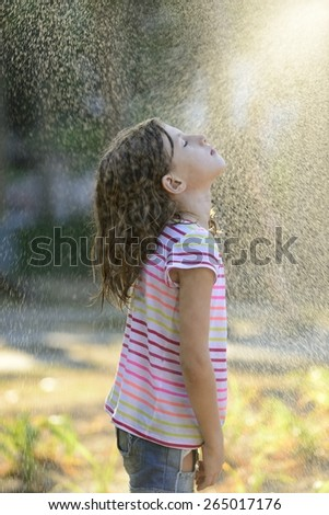 Happy little girl outdoor in a sunny day enjoying the light rain. - stock photo