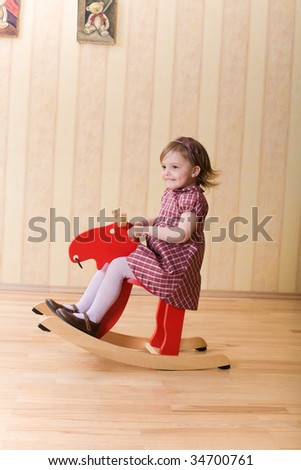 Happy little girl play with toy wooden deer - stock photo