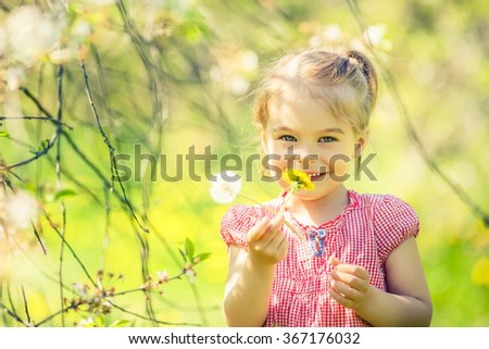 Happy little girl playing in sunny park - stock photo