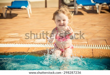 happy little girl playing in the pool - stock photo