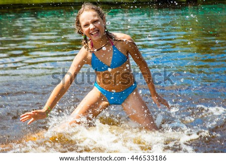 Happy little girl playing in the water - stock photo