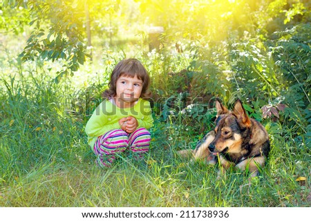 Happy little girl playing with big dog in the garden