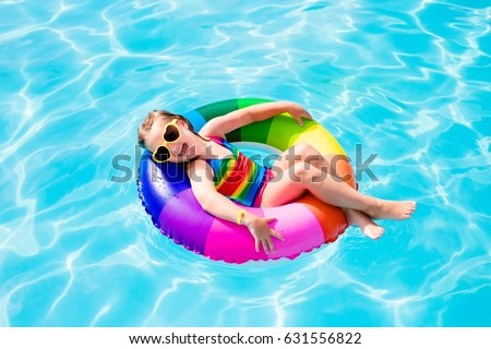 Happy little girl playing with colorful inflatable ring in outdoor swimming pool on hot summer day. Kids learn to swim. Child water toys. Children play in tropical resort. Family beach vacation.