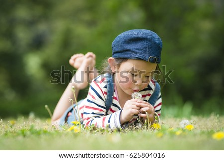 Happy little girl playing with dandelion