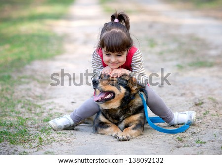Happy little girl playing with dog.  - stock photo