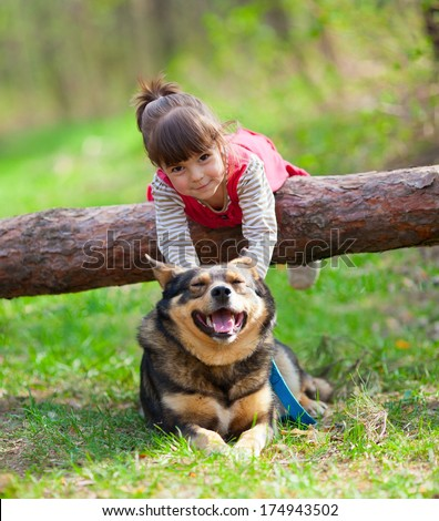 Happy little girl playing with dog in the forest - stock photo