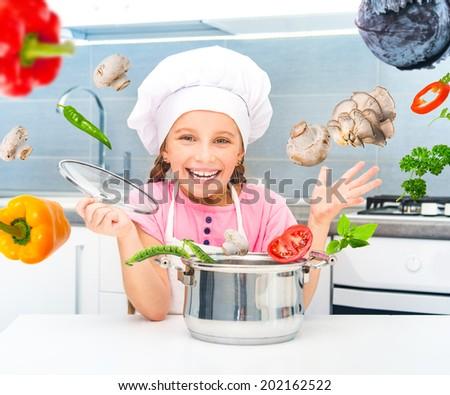 happy little girl preparing vegetarian soup in the kitchen - stock photo