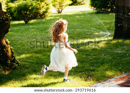 happy little girl running through the spray of water in the park - stock photo