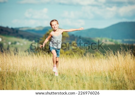 happy little girl runs through a beautiful meadow in the mountains. - stock photo
