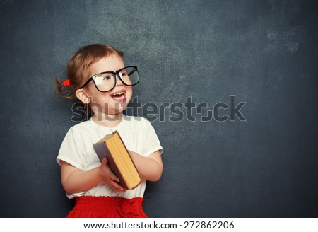happy little girl schoolgirl with a book from the blackboard - stock photo