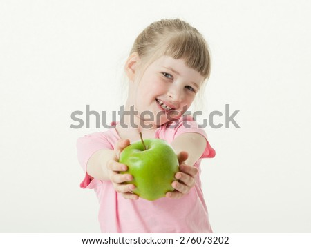 Happy little girl showing a green apple, white background - stock photo