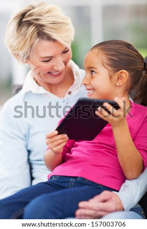 happy little girl showing tablet computer to her grandma at home - stock photo