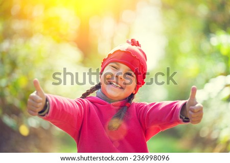 Happy little girl showing thumbs up in sunny day - stock photo