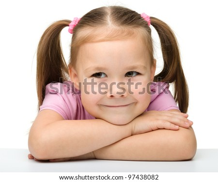 Happy little girl sits at a table and smile, isolated over white - stock photo