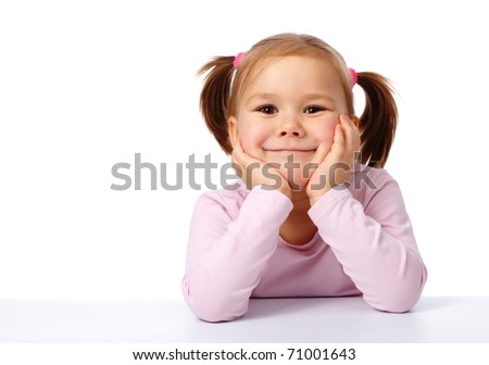 Happy little girl sits at a table and smile, with copyspace on left side, isolated over white - stock photo