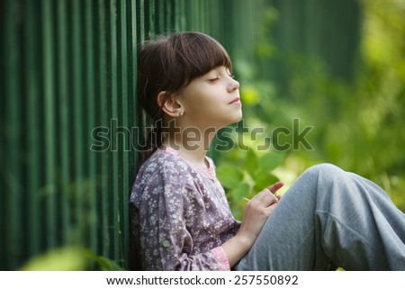 Happy little girl sitting and dreaming about something - stock photo