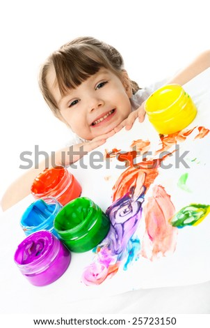 happy little girl sitting by the table and painting with finger paints