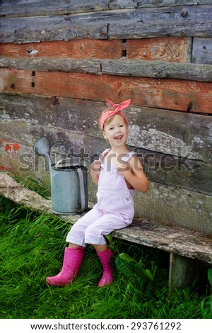 happy little girl sitting on a bench in the garden - stock photo