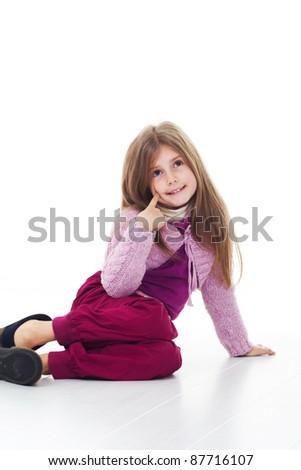 Happy little girl sitting on floor - stock photo