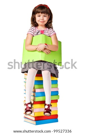 Happy little girl sitting on stack of books. Isolated over white - stock photo