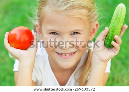 Happy little girl sitting on the grass with a  vegetables at the day time. Concept of healthy food. - stock photo