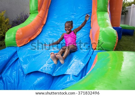 Happy little girl sliding down an inflatable bounce house - stock photo
