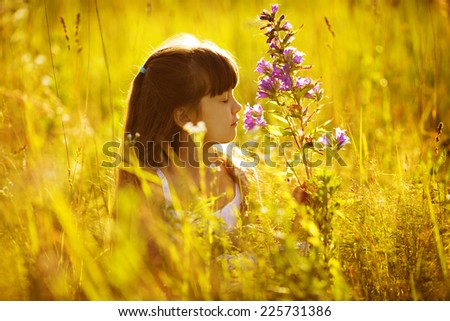 Happy little girl smelling a flower in the field - stock photo
