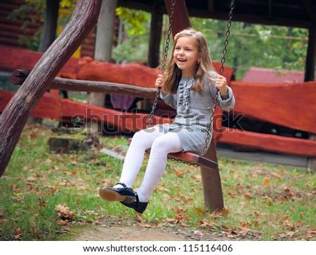 Happy Little Girl Smiling on Swing - stock photo
