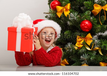 Happy little girl smiling with gift box near the Christmas tree. Christmas concept. - stock photo