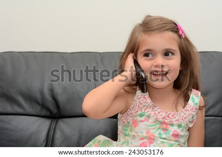 Happy little girl speak on the phone at home. Concept photo of long distance ,call ,communication, telephone, service, overseas, conversation, technology - stock photo