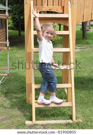 happy little girl standing on ladder - stock photo
