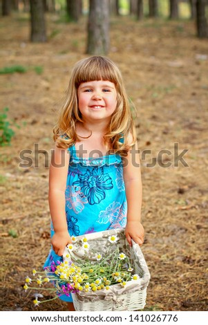 Happy little girl standing with a basket of flowers in  forest - stock photo