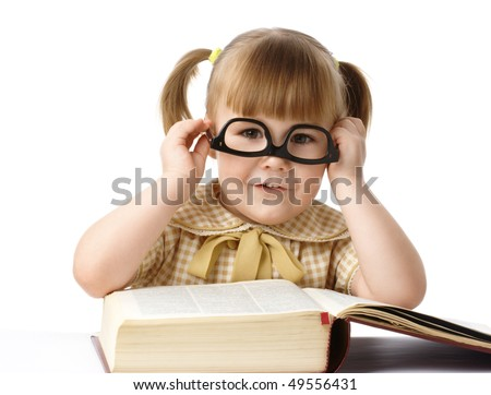 Happy little girl surrounded by books wearing black glasses, back to school concept, isolated over white