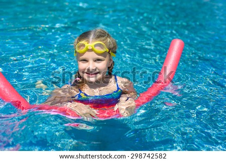 Happy little girl swimming with a pink foam noodle in a pool while on summer vacation - stock photo