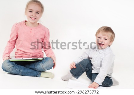 Happy little girl uses a tablet and boy playing with chalk - stock photo