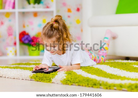 Happy little girl using tablet - stock photo