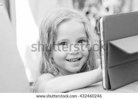 Happy little girl using tablet computer oudoors ( black and white ) - stock photo