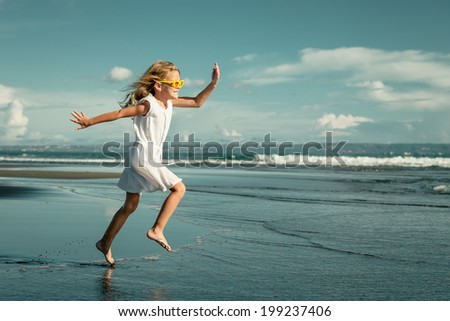Happy little girl  walking at the beach at the day time - stock photo