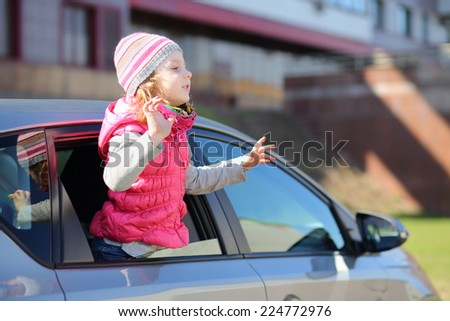 Happy little girl waving her hands out of the car window
