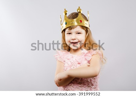 Happy little girl wearing pink dress and metal golden crown, looking at camera, gray studio background, copy space, smiling. - stock photo
