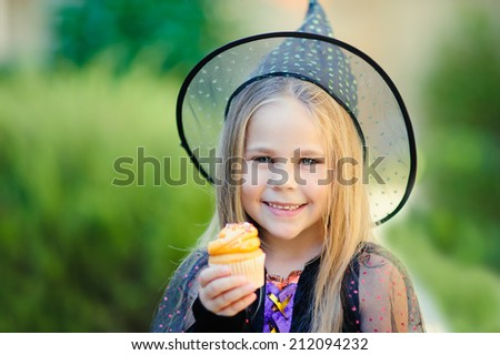 Happy Little girl wearing witch costume eat cupcake on Halloween - stock photo