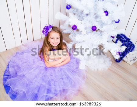 happy little girl with a gift in hands near white Christmas tree - stock photo