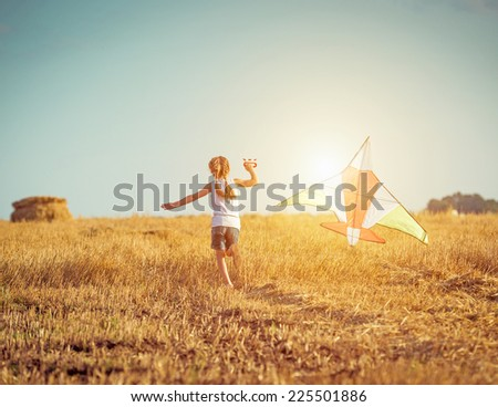 happy little girl with a kite in a field - stock photo