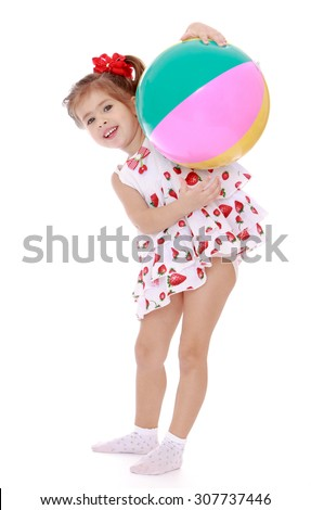 Happy little girl with a short ponytail on the head in which braided red bow plays with inflatable striped ball . The girl is vacationing with his parents on the beach , in the seaside resort-Isolated