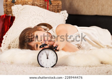 Happy little girl with an alarm clock waiting for Christmas - stock photo