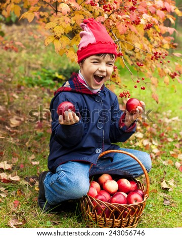 Happy little girl with apples in the garden - stock photo