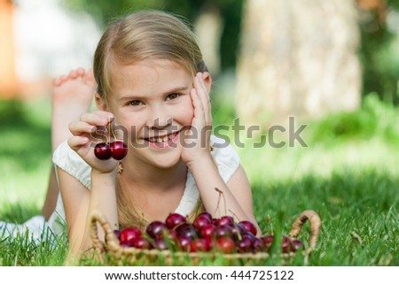 Happy little girl with basket of cherries lying near the tree in the garden  at the day time. Concept of healthy food. - stock photo